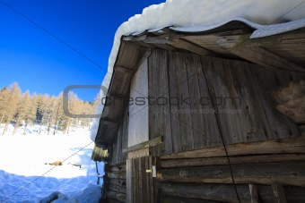 Old barn in winter in the mountains on a sunny day