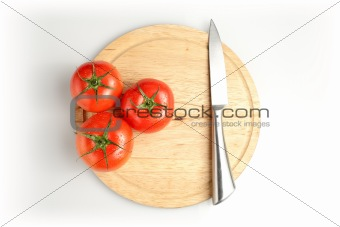 Tomatos and knife on plate