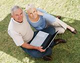 Old couple using laptop in a park