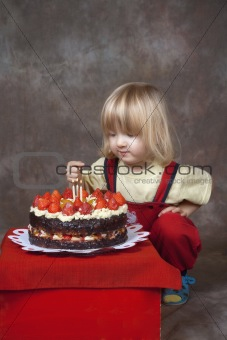 boy with long blond hair watching candles on his birthday cake