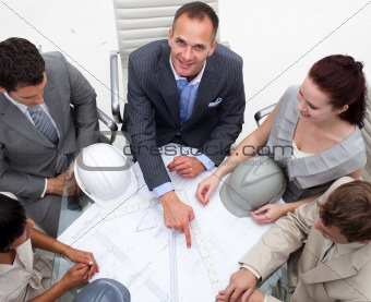 Architect manager pointing at a blueprint in a meeting