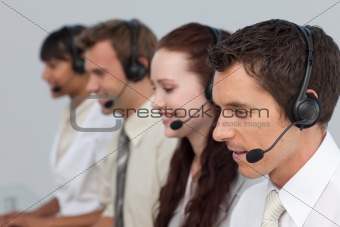 Attractive man with a headset on working in a call center