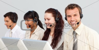 Smiling attractive businessman working in a call center