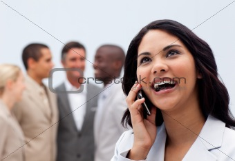 Happy businesswoman on phone with her team in the background