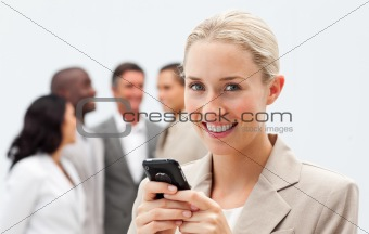 Smiling businesswoman writing a message with a mobile phone