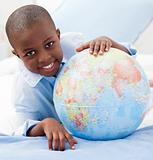 Boy looking at a globe while smiling at the camera
