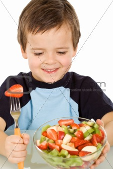 Boy about to eat a large bowl of fresh fruit salad