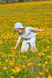 boy with long blond hair picking dandelion standing in a field