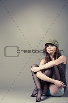 Beautiful young girl sitting with her knees pulled up