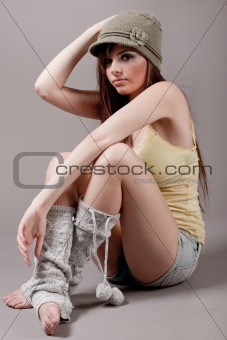 Right pose of a fashion model sitting with cap and woolen leggin