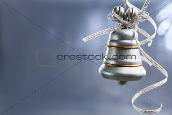 SIlver Christmas bell over blue background