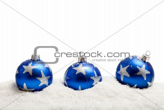 Three blue christmas balls in the snow - isolated