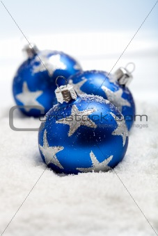 Three blue christmas balls in snow