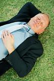 Top view of a middle aged business man sleeping on the grass