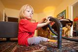 boy with long blond hair helping with vacuum cleaning