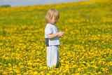 boy with long blond hair holding dandelion standing in a field
