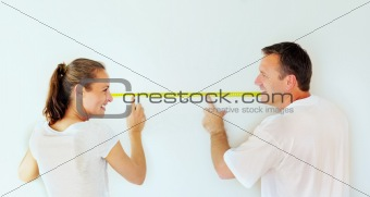 Smiling couple taking wall measurements with a measuring tape