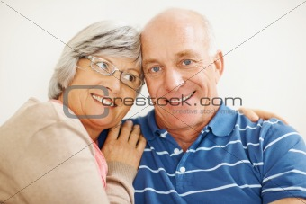 Closeup of a romantic senior wife hugging her husband