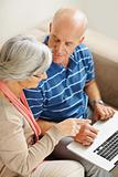 Senior man and woman using a computer laptop