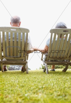 Rear view of a peaceful senior couple sitting on chairs outdoors