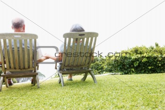 Rear view of a romantic senior couple on chairs outdoors
