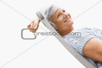 Retired old woman with a lovely smile relaxing on chair
