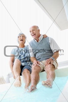 Senior man and woman frolicking by the swimming pool