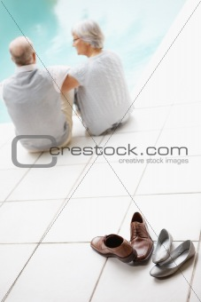 Footwear and rear view of elderly couple at distance by the pool