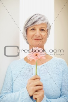 Portrait of a senior woman holding a fresh flower