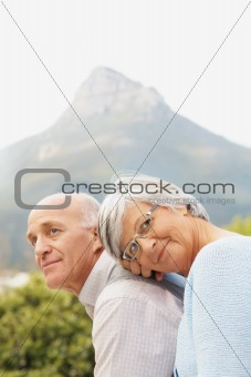 Romantic senior couple sitting against nature background