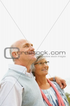 Romantic senior man and woman looking up at copy space