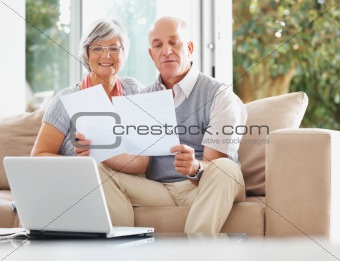 Senior couple with laptop reading documents at their house