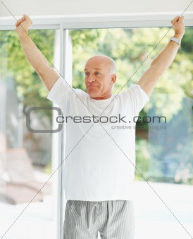Fit senior man stretching over a bright background