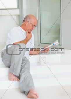 An old senior man reading a newspaper at home