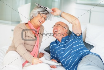 Cheerful senior couple with newspapers having fun on bed