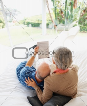 Relaxed senior man and woman reading newspaper on bed