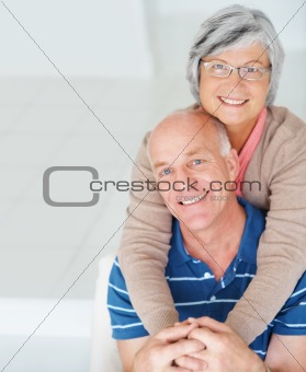 Romantic senior woman embracing her happy husband from behind