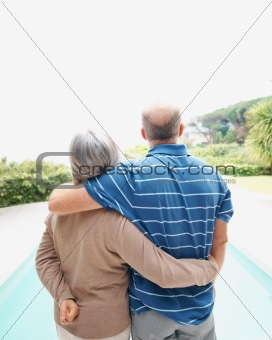 Rear view of loving senior couple standing by the swimming pool