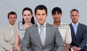 Multi-ethnic business team sitting in front of the camera