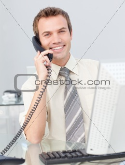 Attractive young businessman talking on phone in the office