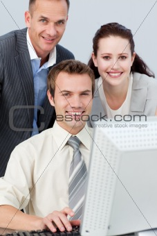 Smiling business people working together with a computer