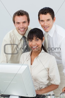 Smiling business people using a computer in the office