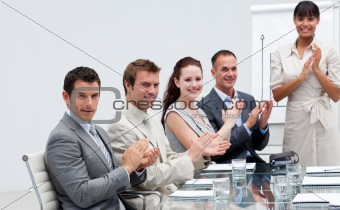 Business people applauding a colleague after reporting to sales