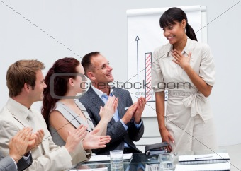 Business team applauding a colleague after giving a presentation
