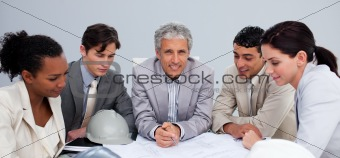Architect manager in a meeting with his team studying plans
