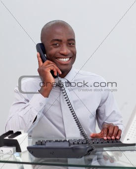 Smiling Afro-American businessman on phone in the office