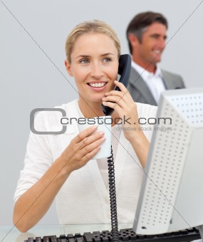 Beautiful businesswoman drinking coffee and talking on phone