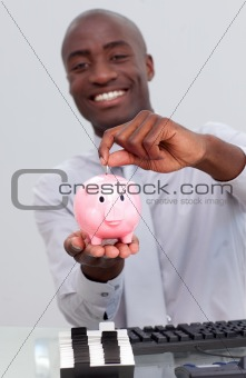 Happy Afro-American businessman saving money in a piggybank