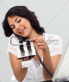 Attractive businesswoman on phone and looking at an index holder in the office