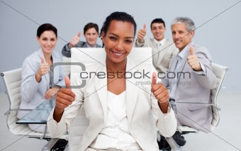 Afro-American businesswoman and her team with thumbs up